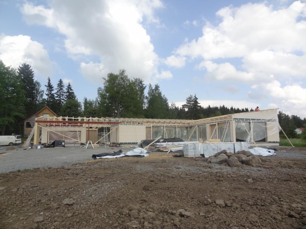 Toisen pystytyspäivän iltapäivällä talo alkoi saada muotoaan. Etupihalle on kuormattu toimitukseen kuuluvaa puutavaraa. Kyprocit nostettiin autokatokseen, joten ne olivat hyvässä sateensuojassa heti kun katto saatiin päälle.
