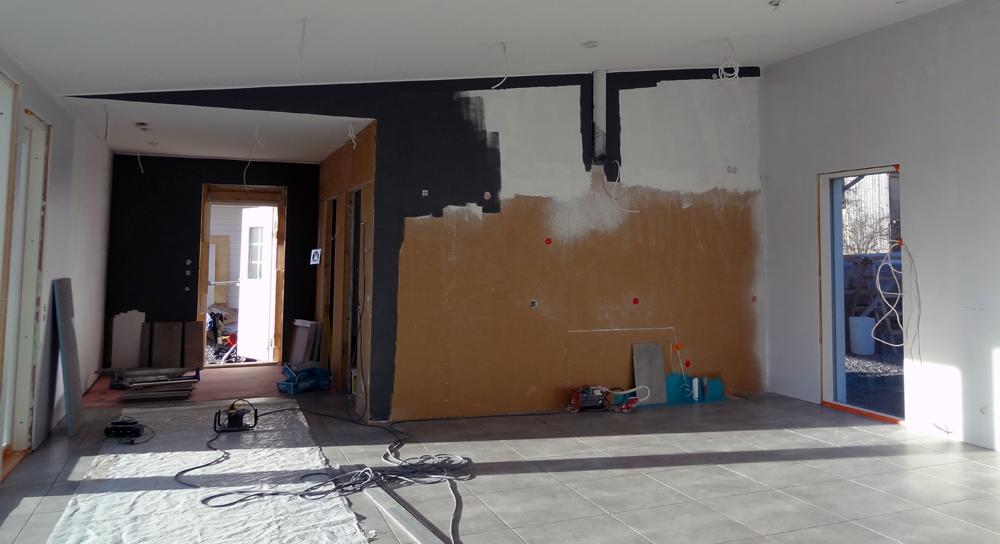 Kuvateksti: Ennen maalausta viimeistelimme seinän ja katon rajat akryylillä ja maalasimme seinän yläosan paperinvalkoisella (F497). Tämän jälkeen maalasimme seinien yläosat telarajaajalla ja jatkoimme telalla. Tumma väri on kuvassa vedetty kahteen kertaan ja oikean puoleinen vaalean harmaa seinä yhteen kertaan.