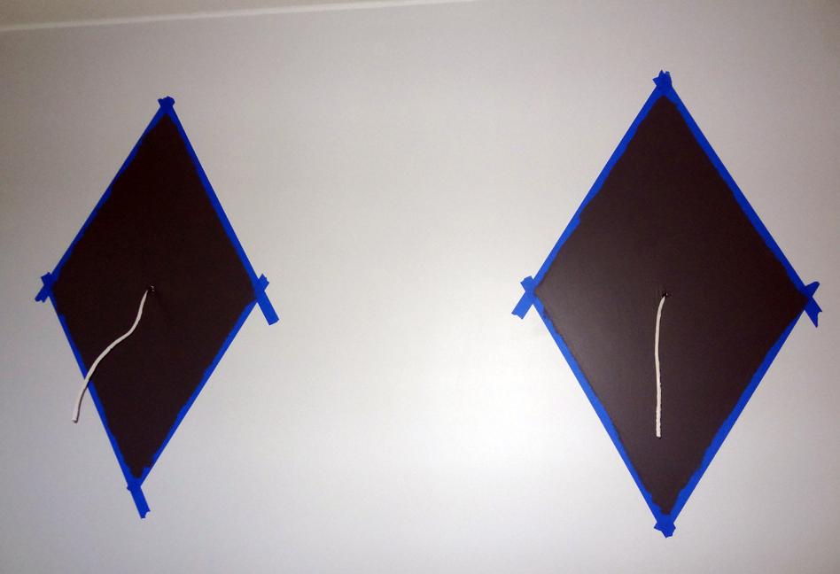 Kuvateksti: Nämä salmiakkikuviot ehdimme maalata mh2:n seinään ennen muuttoa sisään. Muut tehostemaalaukset ovat vieläkin maalaamatta. Käytimme rajaamiseen sinistä rajausteippiä – mutta emme olleet tyytyväisiä lopputulokseen, joten korjailimme maalauksia vielä perinteisellä maalarinteipillä. Ja paljon parempi tuli.